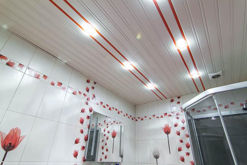 Белый реечный потолок с красными вставками в ванной комнате